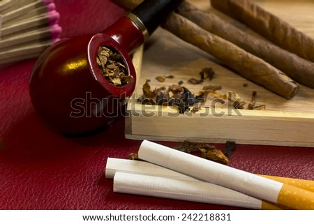 Pipe, tobacco, cigarettes, cigars, smoking, etc. on red leather background  Royalty-Free Stock Photo #242218831
