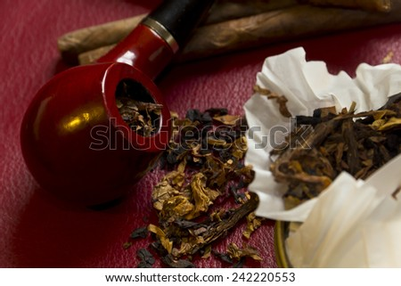 Pipe, tobacco, cigarettes, cigars, smoking, etc. on red leather background  Royalty-Free Stock Photo #242220553