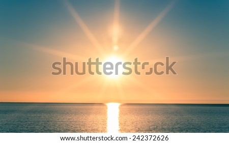 Sunset over Ocean - Bright Orange Sun Setting on Beautiful Blue Water #242372626