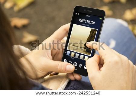 modern social photography concept: young woman using photo editor app on the smartphone at the park