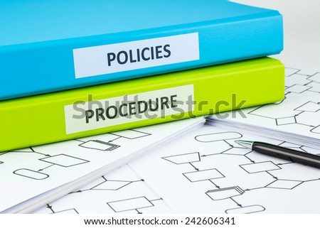 Document binders with POLICIES and PROCEDURE words on labels place on blank process flow charts with pen Royalty-Free Stock Photo #242606341