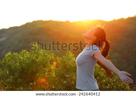 cheering woman open arms at sunrise mountain peak wellness concept Royalty-Free Stock Photo #242640412