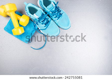 Sneakers and dumbbells fitness on a gray background. Different tools for sport #242755081