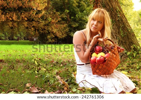 young woman in a park, holding a basket of fresh fruits in the garden abundance and natural beauty and healthy life concept #242761306