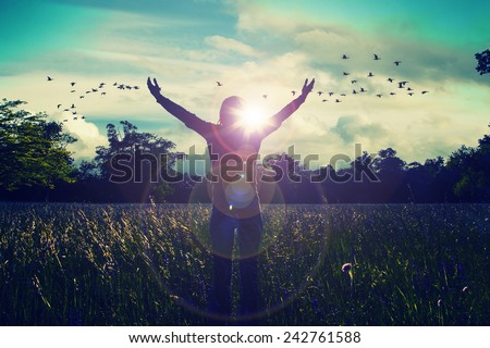 Young girl spreading hands with joy and inspiration facing the sun,sun greeting,freedom concept,bird flying above sign of freedom and liberty Royalty-Free Stock Photo #242761588