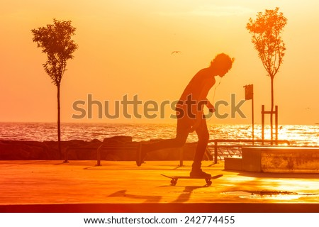 Young skaters training in the park near the sea in sunset. Toned picture