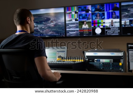 TV engineer at editor in studio. TV editor working with vision mixer in a television broadcast gallery.Man sat at a vision mixing panel in a television studio gallery