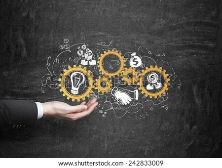 hand holding gold gears with business icons