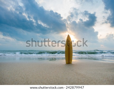 Surfboard on the beach at sunset #242879947