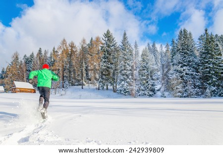 Young man in green jacket running in deep snow #242939809