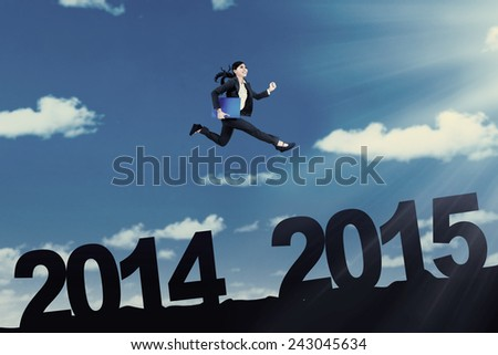 Young entrepreneur holding document and jumps in the sky over number 2014 to 2015 #243045634