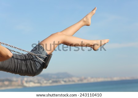 Hair removed woman legs swinging on the beach with the sky in the background #243110410