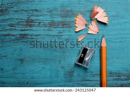 Pencil with sharpening shavings on color wooden background Royalty-Free Stock Photo #243125047