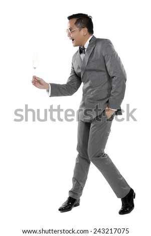 Elegant young fashion man in gray suit raising a glass of champagne on the white background. #243217075