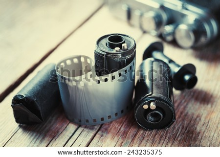 Old photo film rolls, cassette and retro camera on background. Vintage stylized.