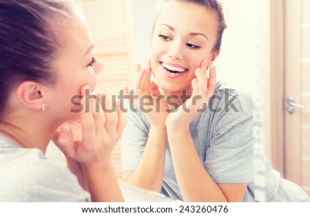 Beauty skin care. Young beautiful teenage girl touching her face before the mirror, enjoying her clean skin. Pretty woman touching her cheek and smiling. Perfect pure skin. Fresh Clean Skin. Skincare  #243260476