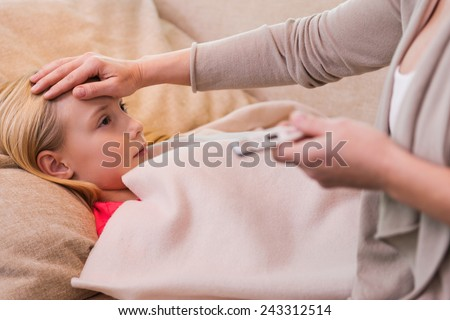 I hope it is not flu. Mother holding thermometer and touching forehead of her ill daughter lying on the couch  #243312514