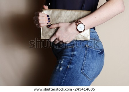 Stylish woman in jeans with small gold clutch and watch . fashion concept.  Royalty-Free Stock Photo #243414085