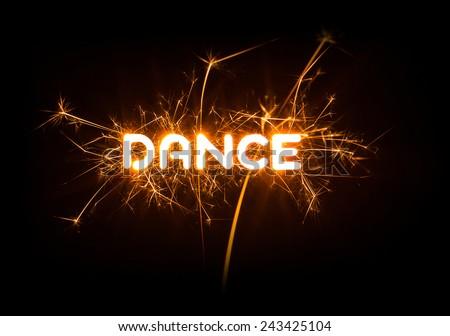 DANCE word in glowing sparkler on dark background.