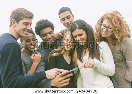 Multiethnic Group of Friends Looking at Mobile Phone Royalty-Free Stock Photo #243484990