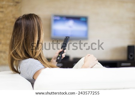 Young woman watching TV in the room Royalty-Free Stock Photo #243577255