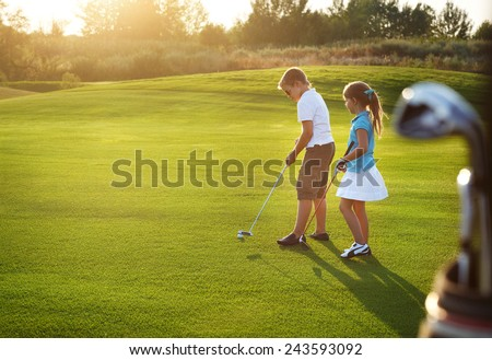 Casual kids at a golf field holding golf clubs. Sunset #243593092