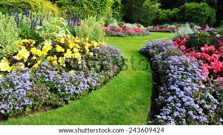 Colourful Flowerbed and Grass Path in a Beautiful Garden #243609424