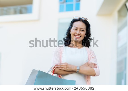 Portrait of mature Vietnamese woman holding shopping bags #243658882