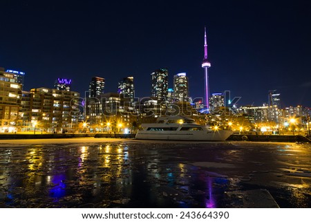 TORONTO, CANADA - 12TH JANUARY 2015: Part of the Toronto Skyline in the winter showing frozen water in the lake #243664390