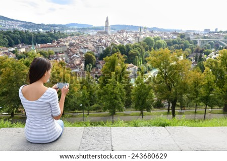 Tourist with smart phone camera in Bern, Switzerland at Rosengarten, the Rose Garden view. Woman taking photograph with smartphone at enjoying view of Berne landmarks and tourist attractions. #243680629