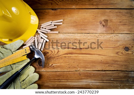 hammer, protective gloves, wooden dowels   and yellow safety helmet on wooden background #243770239