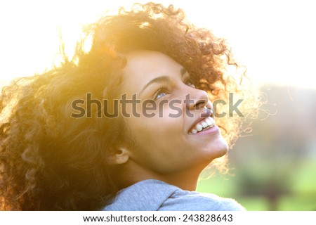 Close up portrait of a beautiful young african american woman smiling and looking up Royalty-Free Stock Photo #243828643