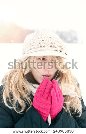 winter woman in snow photo, blows breath to her hands outside on cold winter day. Portrait Caucasian female model with pink gloves and white hat with scarf in first snow
