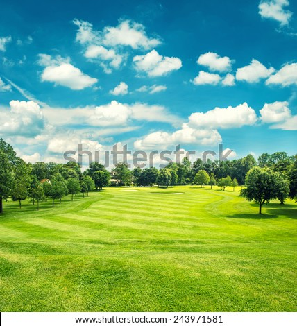 Golf field and blue cloudy sky. Beautiful landscape with green grass. Retro style toned picture