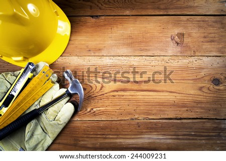 hammer, protective gloves, folding ruler, model knife  and yellow safety helmet on wooden background #244009231