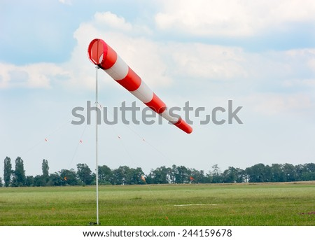 Windsock against cloudy sky. Airfield with green grass. #244159678