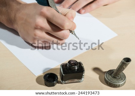 Writing with feather. Close-up of man writing with feather pen with ink bottle #244193473