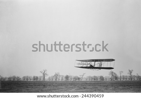 Orville Wright 1871-1948 in flight over treetops covering a distance of approximately 1 760 feet in 40 1/5 seconds at Huffman Prairie Dayton Ohio. November 16 1904. #244390459