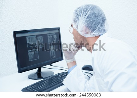 Concentrated male dentist looking at x-ray on computer #244550083