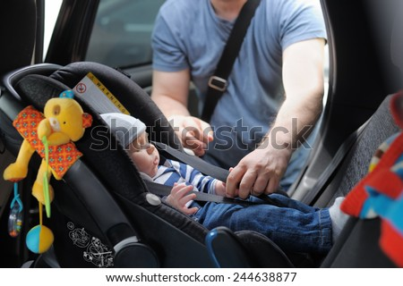 Father fasten his little son in car seat Royalty-Free Stock Photo #244638877