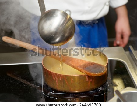 Chef is pouring broth in boiling risotto #244695700