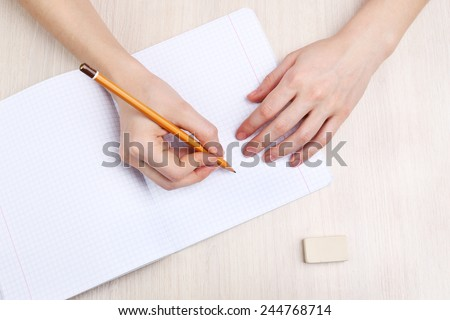 Human hands with pencil writing on paper and erase rubber on wooden table background #244768714