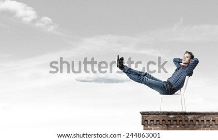 Young man sitting in chair with legs up and relaxing #244863001