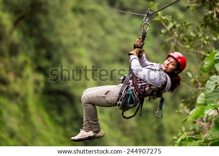 Adult Tourist Wearing Casual Clothing On Zip Line Trip Selective Focus Against Blurred Forest #244907275