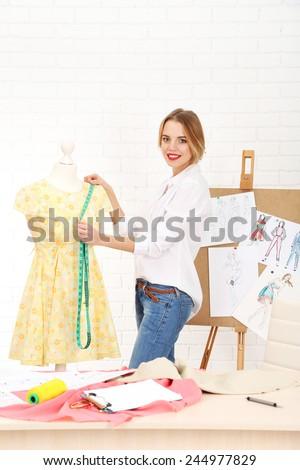 Beautiful young dressmaker in workroom #244977829