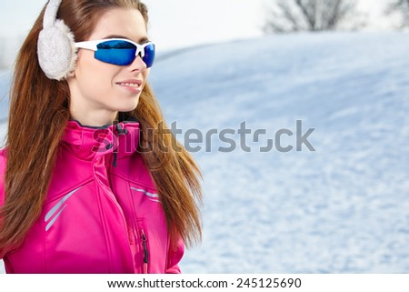 Beautiful woman wearing goggles in snowy winter outdoors  #245125690