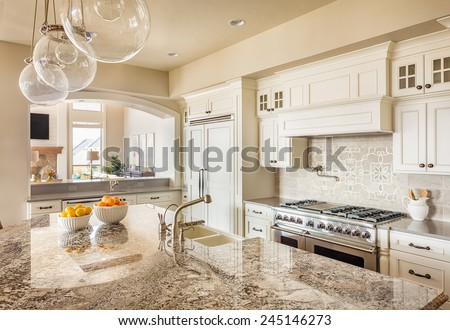 Beautiful New Kitchen Interior with Island, Sink, Cabinets and Pendant Lights in New Home #245146273