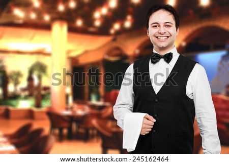 Young waiter at the restaurant Royalty-Free Stock Photo #245162464