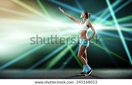 Young attractive fitness girl against stage blurred lights #245168053