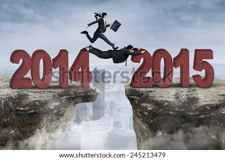 Two businesspeople cooperate through an obstacle from number 2014 to 2015 #245213479
